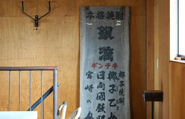 倉庫にあった焼酎の銘柄〈銀滴〉の看板。解体時に廃棄するのがもったいなく、いまでも大事に事務所に飾っている。