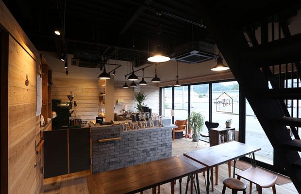 壁は飫肥杉の下見板張りを白塗装し、床には足場板を敷いた。カウンター横のテーブルはカフェスペースとして、淹れたてのコーヒーを楽しむことができる。