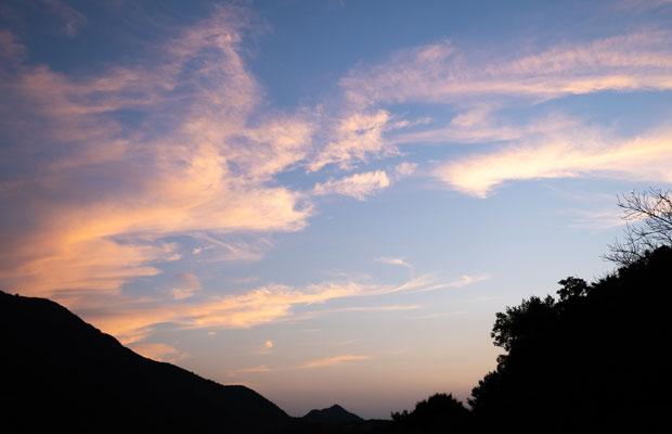 秋の夕空。夕陽に照らされて少しピンクがかった雲が美しい。