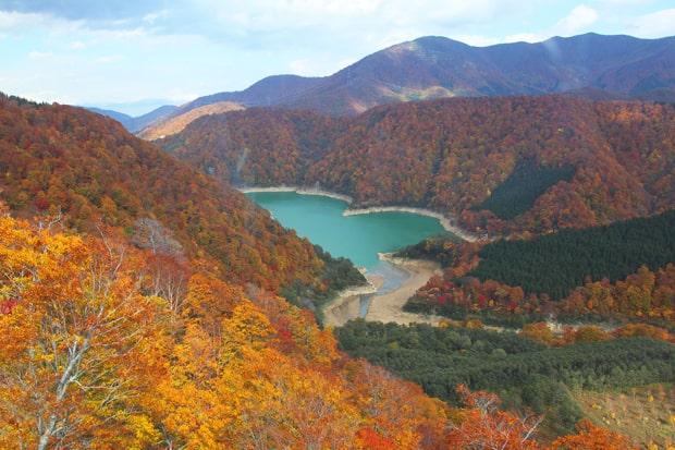 まるで紅葉の絨毯。鮮やかなエメラルドグリーンの二居湖(ふたいこ)も美しい。