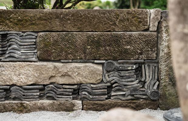 庭に新設した石垣。以前使用されていた瓦を石垣の間に入れ、歴史のかけらを敷地内に残す。