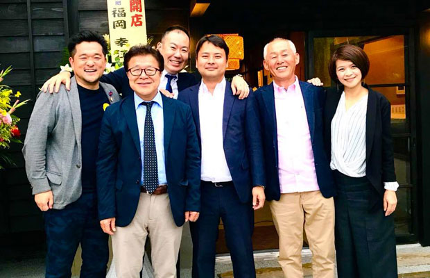 オープン時、仲間から祝福を受ける本田清大さん(右から3番目)。